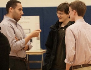 """Svante Myrick in conversation with Jeff Stein (in black), the person behind """"Ithaca Voice,"""" and a city hall intern."""